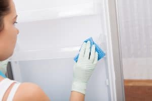 Rear View Of A Young Woman Cleaning Refrigerator