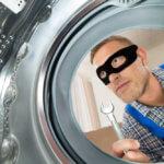 Young Repairman With Burglar mask Looking Inside The Washing Machine