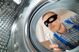 Young Repairman With Burglar mask Looking Inside The Washing Machine