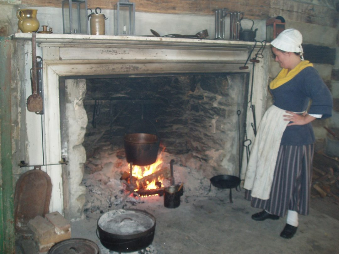 Woman standing by large fireplace with cauldron
